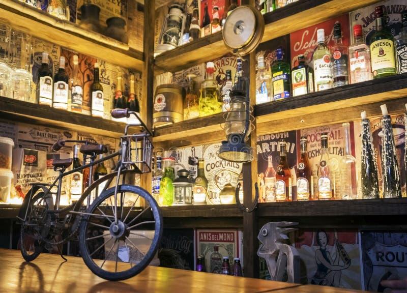 Houten barteller met een showcase van diverse alcohol in BarVhlam stock foto