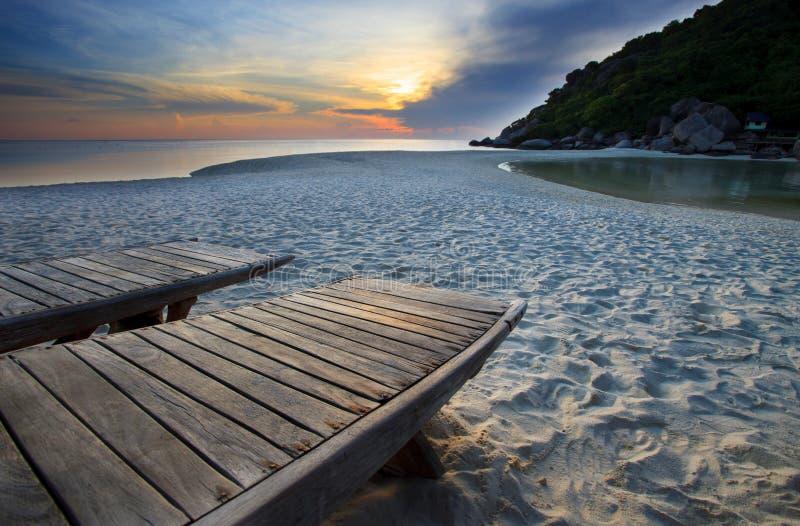 Houten bed op strand in duistere hemel royalty-vrije stock afbeelding