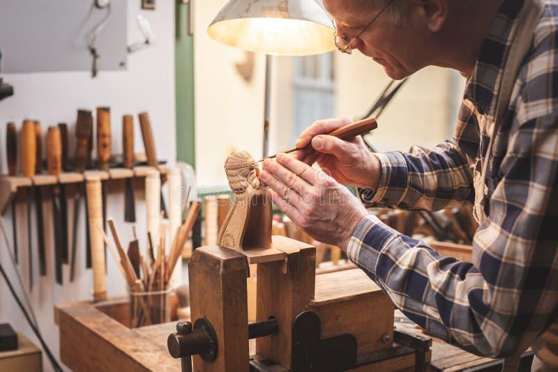 Houten beeldhouwer bij een werkbank die een houten cijfer snijden stock foto