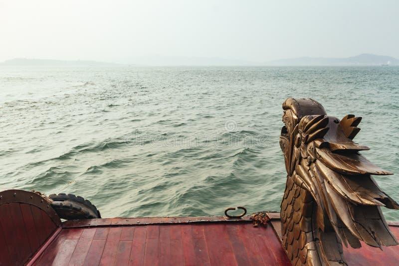 Houten beeldhouwwerk van draakhoofd bij de rug die van toeristencruise zich op smaragdgroen water in gouden uur in Quang Ninh, Vi stock afbeeldingen