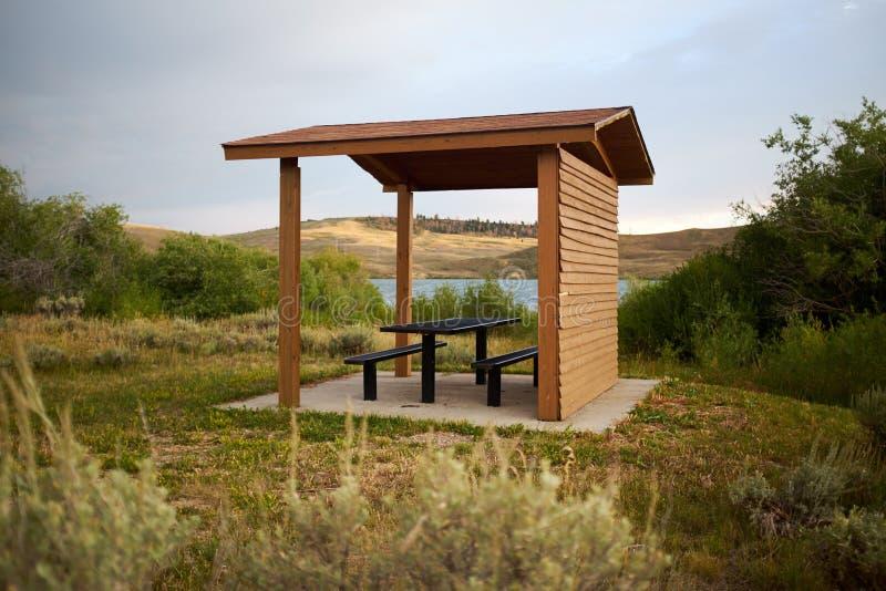 Houten behandelde picknickhut met lijst en stoelen stock afbeelding