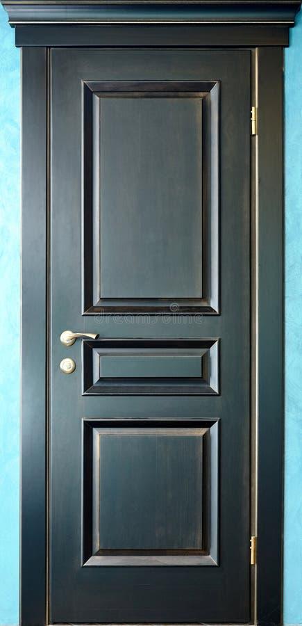 Houten binnenlandse zwarte en gouden deur van ebbehout met messingsmetaal stock afbeelding