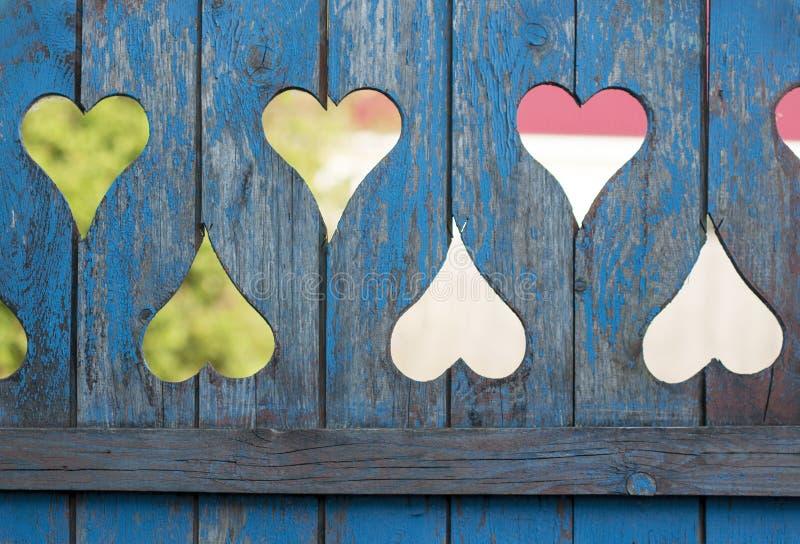 Houten blauwe oude omheining met gaten in de vorm van harten stock afbeelding