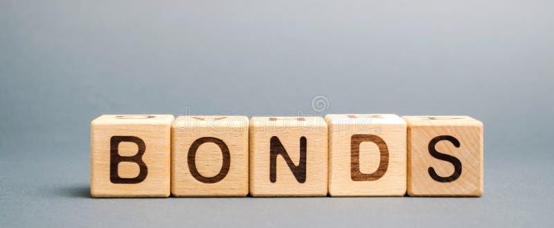 Houten blokken met de woordbanden Een band is een veiligheid die erop wijst dat de investeerder een lening aan de uitgever heeft  stock afbeeldingen