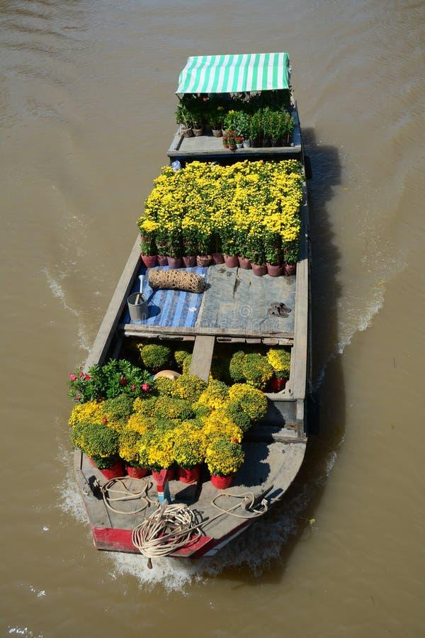 Houten boot dragende bloemen aan de het drijven markt in Ben Tre, Vietnam royalty-vrije stock foto's