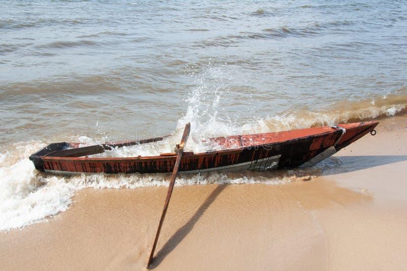 Houten boot op de kust van meer Baikal en waterplonsen stock afbeelding