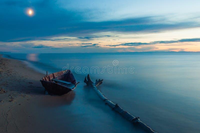 Houten boot op de kust van meer Baikal in het maanlicht in de avond stock foto's