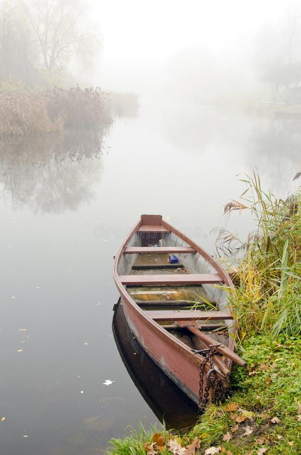 Houten boot op kust van rivier die in dichte mist is gedaald. stock foto
