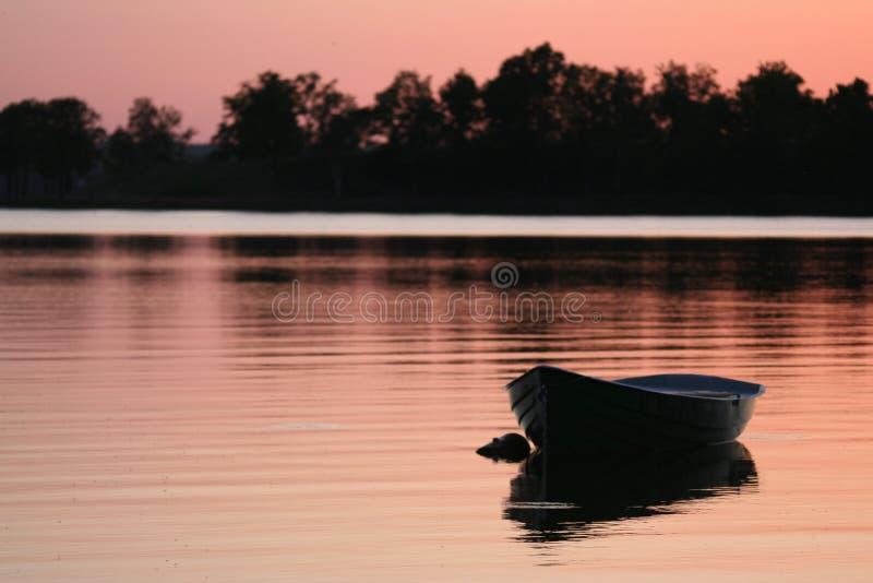 Houten boot op zonsondergang royalty-vrije stock foto