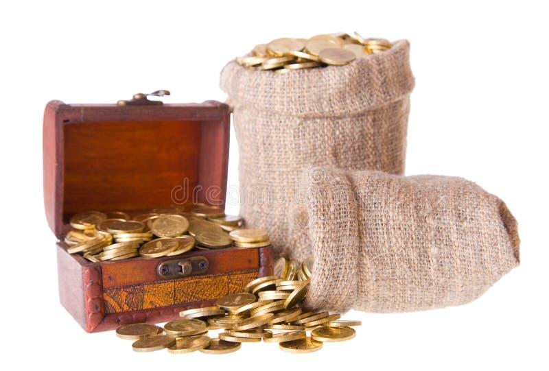 Houten borst en twee zakken die met muntstukken wordt gevuld stock afbeeldingen