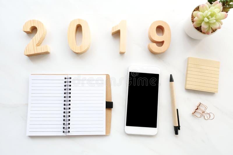 2019 houten brieven, leeg notitieboekjedocument, witte smartphone met het lege scherm en potlood op witte marmeren lijstachtergro stock foto's