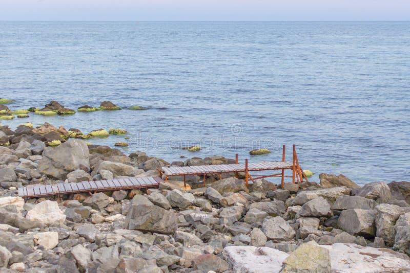 Houten brug aan het overzees onder het steenstrand stock fotografie