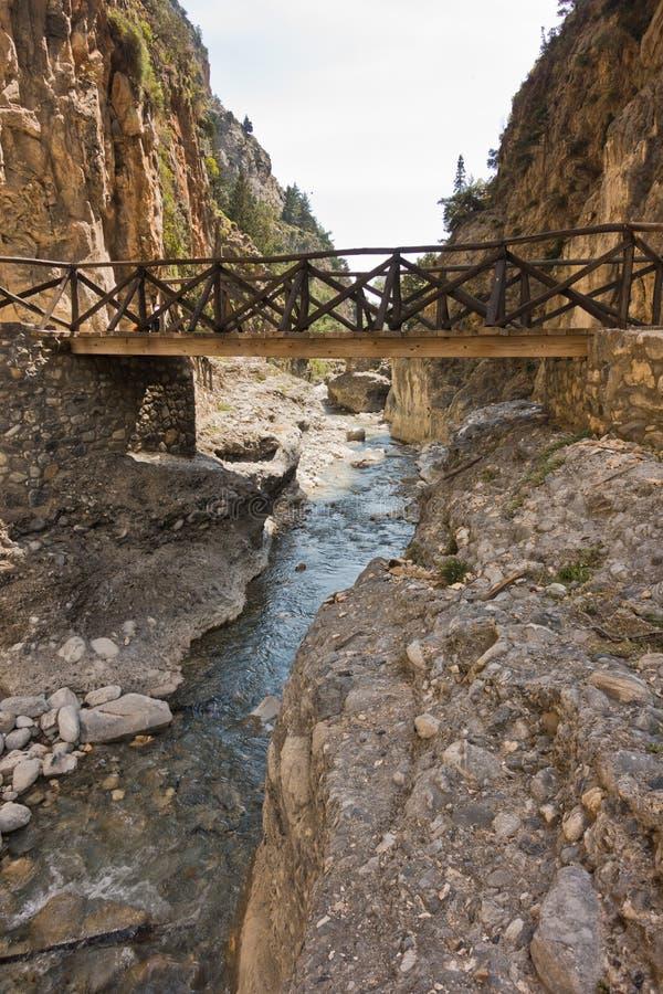 Houten brug over bergrivier bij rotsachtig terrein van Samaria-kloof, zuidwestendeel van het eiland van Kreta stock afbeelding