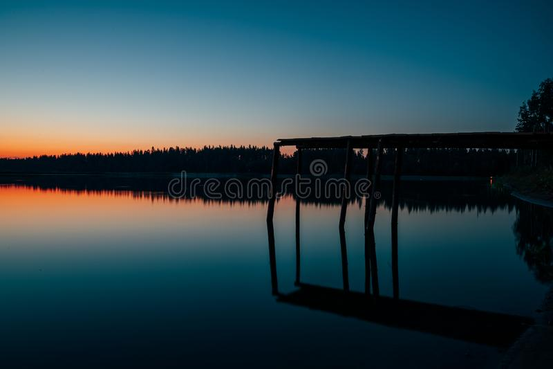 Houten brug waarvan sprong in het meer bij nacht royalty-vrije stock afbeeldingen