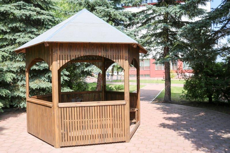 Houten bruin paviljoen voor rust op een achtergrond van groene sparren stock foto's