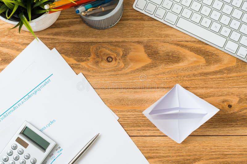 Houten bureau met witte origamiboot stock fotografie