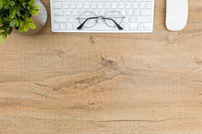 Houten bureaulijst met van het van de computertoetsenbord, muis en oog glazen De hoogste mening met vlakke exemplaarruimte, legt royalty-vrije stock afbeelding