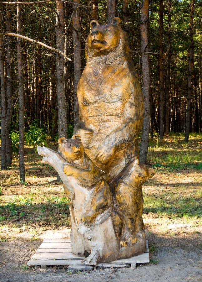 Houten cijfer van een beer met een teddybeer, pretpark 'Nelzha ', Voronezh-gebied stock afbeelding