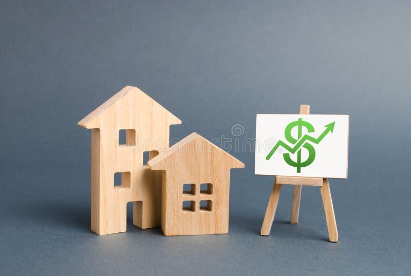 Houten cijfers van huizen en een affiche met groene omhoog pijl Het concept de groei van de onroerende goederenwaarde Verhogingsv stock foto