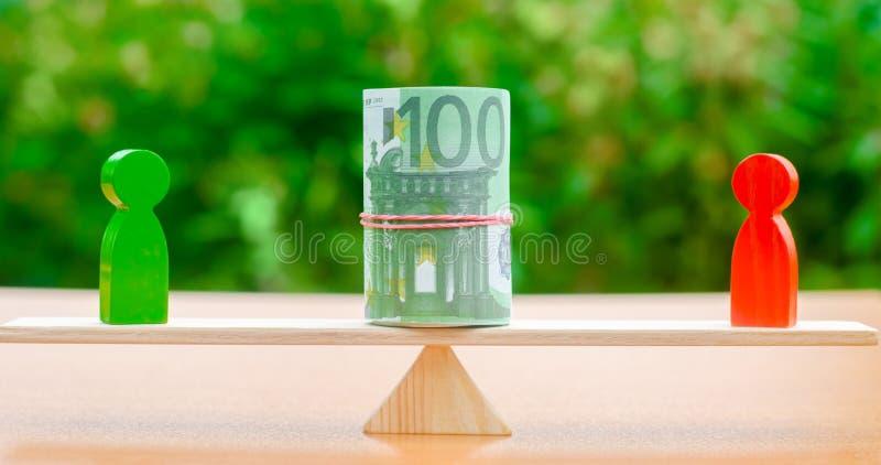 Houten cijfers van mensen op schalen en euro bankbiljetten tussen hen Het concept scheiding van geld Bezitsafdeling scheiding stock foto's