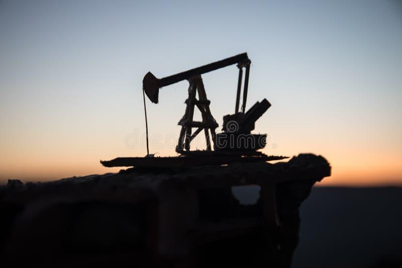 Houten decoratie Van de het booreilandenergie van de oliepomp de industriële machine voor aardolie op de zonsondergangachtergrond stock afbeeldingen