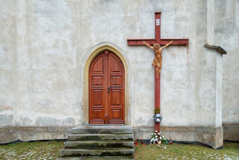 Houten deur aan de kerk en een groot kruis op de muur Vier kaarsen Christelijke traditie stock afbeelding