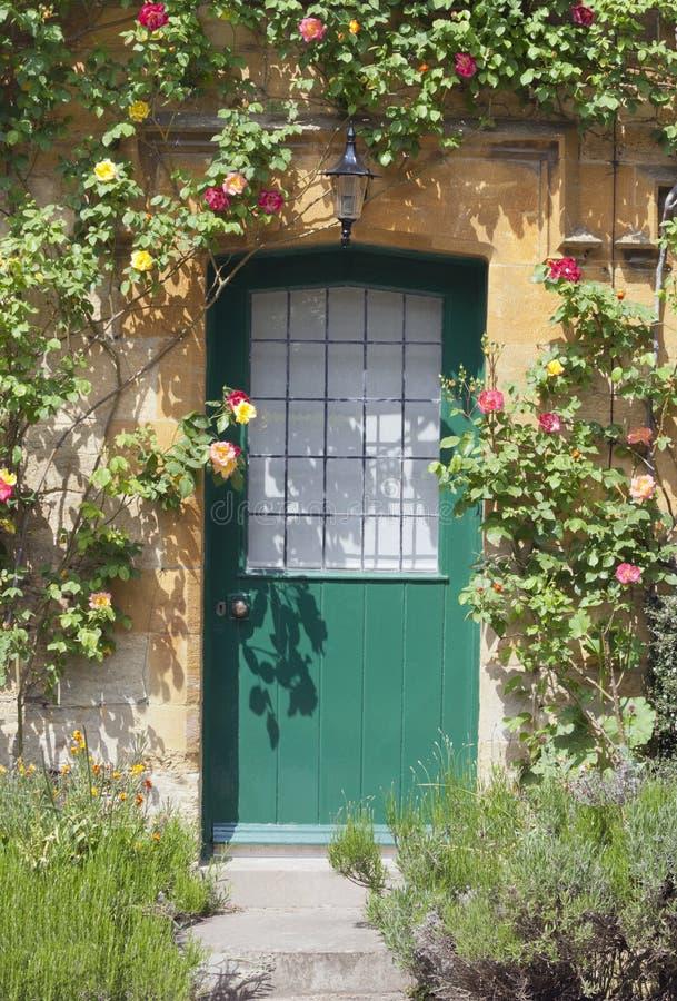 Houten deuren in Cotswolds-plattelandshuisje met het hangen van rozen stock afbeelding