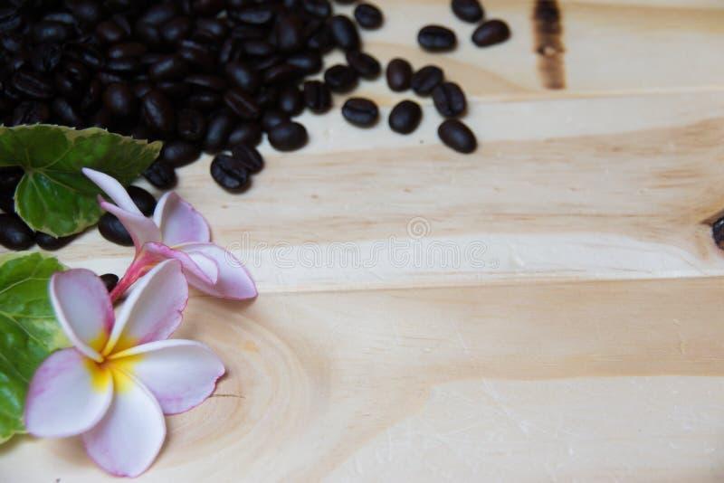 Houten die achtergrond met koffiebonen, frangipanibloemen en bladeren wordt verfraaid stock afbeelding