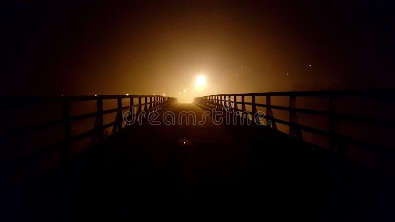 Houten die brug bij nacht met mist en stadslichten op achtergrond wordt omringd stock foto's