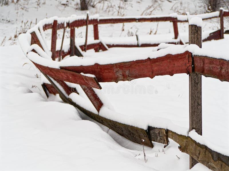 Houten die omheining voor vee met sneeuwclose-up wordt behandeld Oude instortende omheining van geschilderde raad stock afbeeldingen