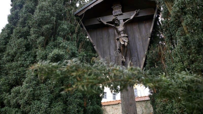 Houten die ori?ntatiepunt met Christus op kruis wordt gekruisigd Art Weergeven van houten monument van gekruisigd Jesus Christ di stock afbeelding