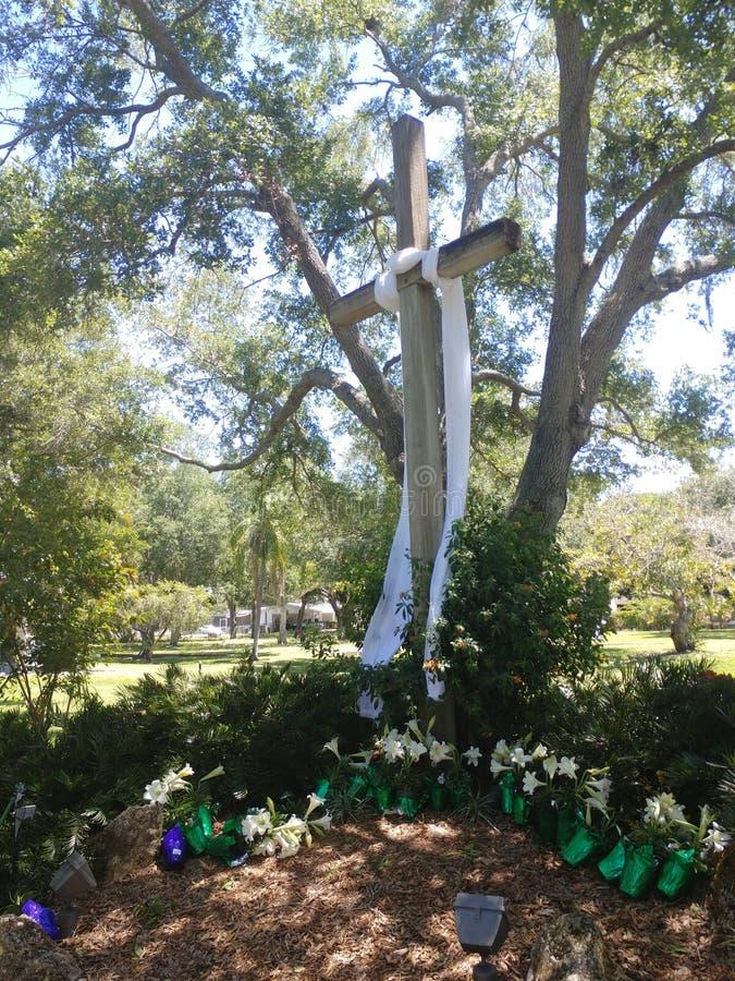 Houten die Pasen-kruis met wit onder majestueuze eiken bomen wordt versluierd stock afbeelding