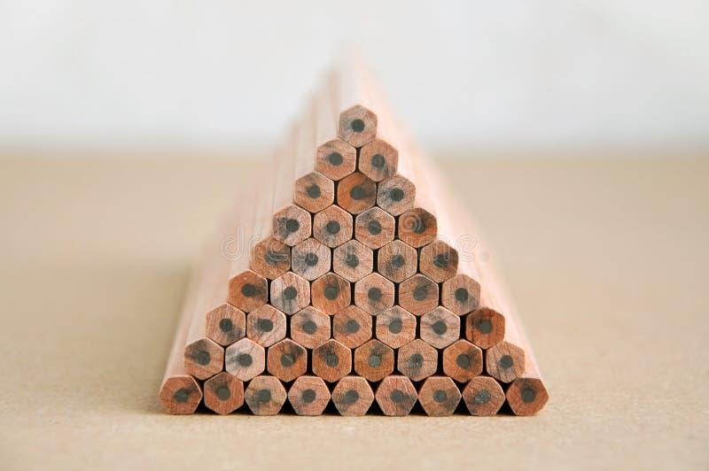 Houten die potloden in een piramidevorm worden gestapeld stock fotografie