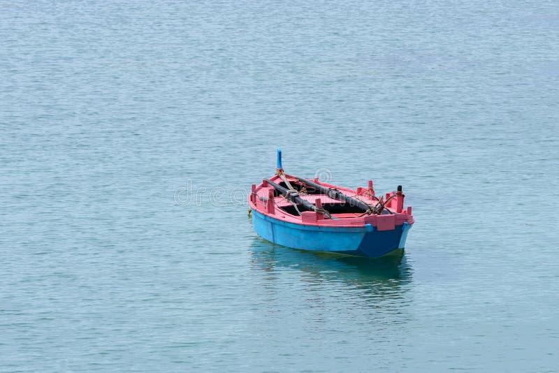 Houten die vissersboot in het overzees wordt vastgelegd royalty-vrije stock fotografie