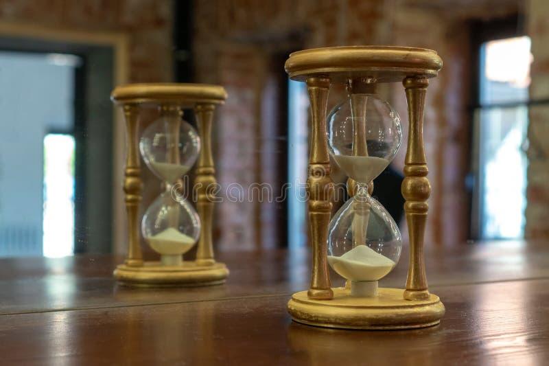 Houten die zandloper in de spiegel wordt weerspiegeld Zandloper op een bruine lijst royalty-vrije stock foto's