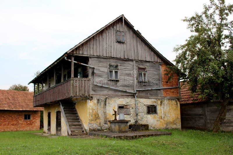 Houten dilapidated oud familiehuis met steenstichting en groot voordiebalkon met ongesneden gras en goed met hand wordt omringd royalty-vrije stock foto
