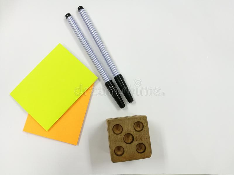 Houten dobbel gezet op witte achtergrond houten dobbel gezet dichtbij 2 zwarte pennen en document nota stock afbeelding