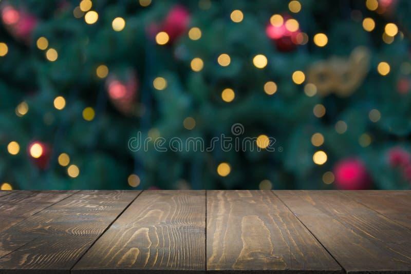 Houten donker tafelblad en vage Kerstmisboom bokeh Kerstmisachtergrond voor vertoning uw producten royalty-vrije stock foto's