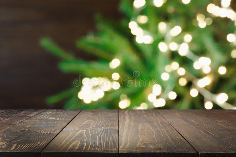 Houten donker tafelblad en vage Kerstmisboom bokeh Kerstmisachtergrond voor vertoning uw producten royalty-vrije stock afbeelding