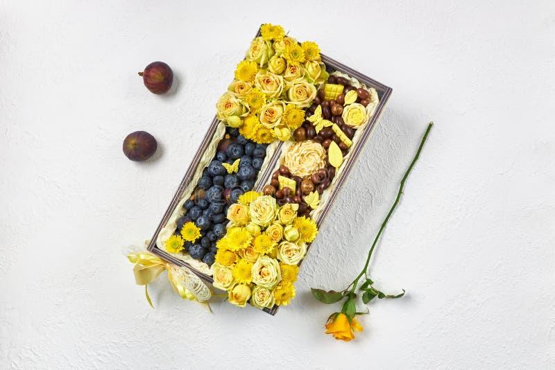 Houten doos gevuld met gele bloemen, blauwe bessen en chocolade op een witte achtergrond royalty-vrije stock afbeeldingen