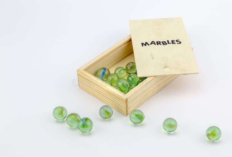 Houten doos groen glasmarmer op witte achtergrond royalty-vrije stock foto