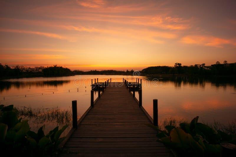 Houten gang in het meer met natuurlijk landschap van zonsondergang en stock foto's