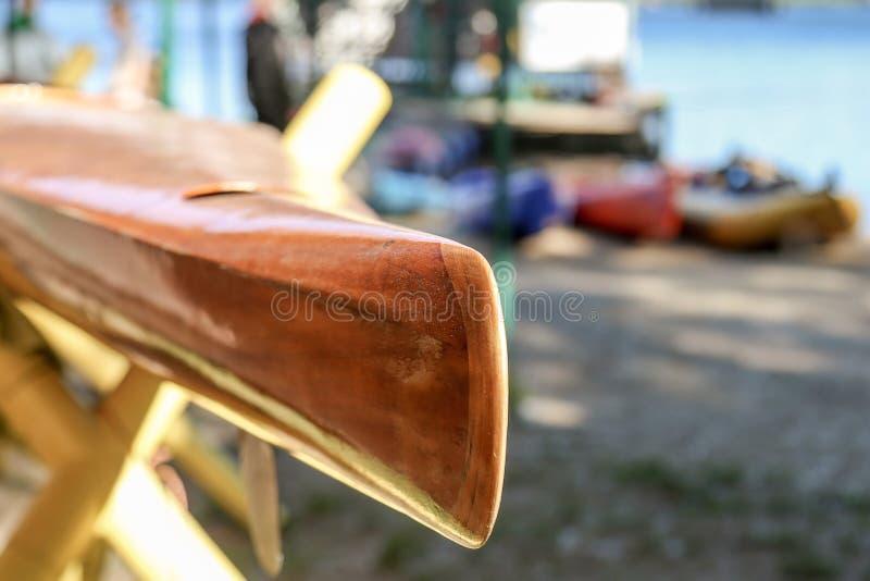Houten gebouwde uitstekende kajak op een rivierkust Moderne kajaks op de achtergrond stock foto