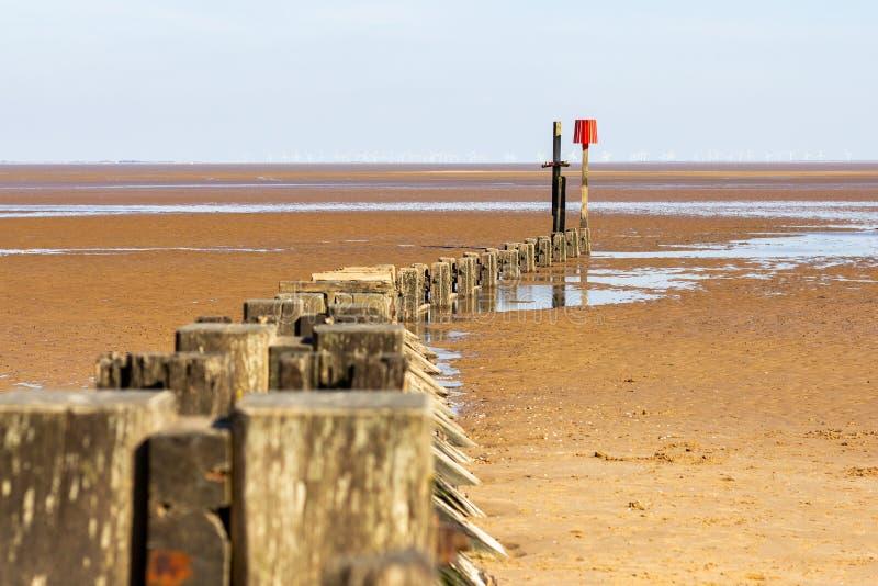 Houten golfbreker op Cleethorpes-strand met windturbines in de afstand royalty-vrije stock afbeeldingen