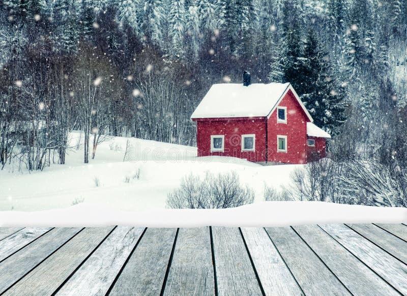 Houten grijs met rood huis in het sneeuwen op de winter royalty-vrije stock foto