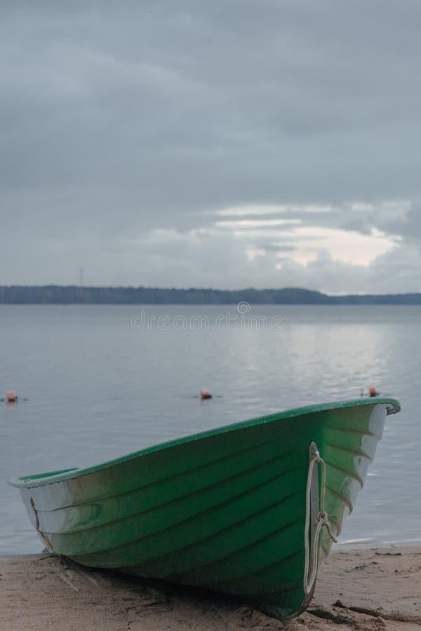 Houten groene boot op een zandig strand op een meer stock afbeelding