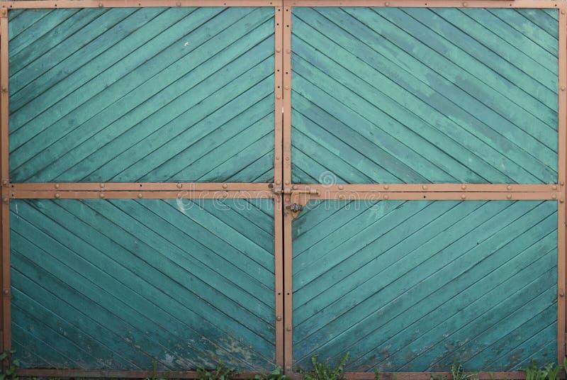 Houten groene poortdeur met oranje hoeken en gras op een grond stock fotografie