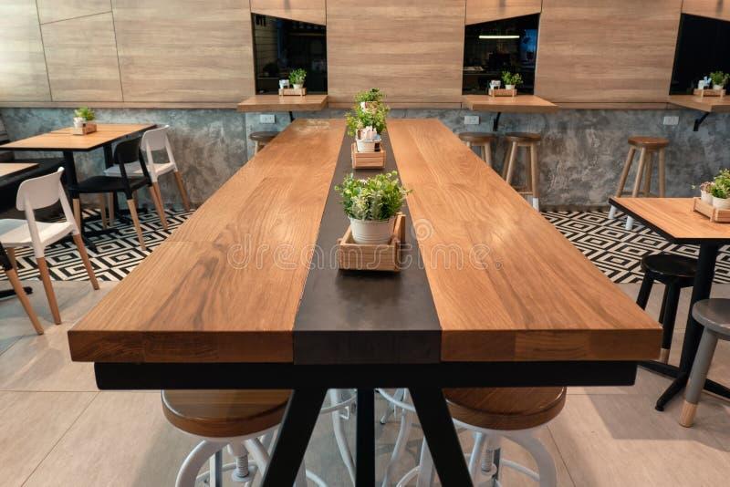 Houten grote lijst met stoelen en installatiedecoratie stock foto