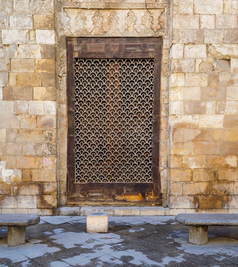 Houten grungevenster met verfraaid ijzernet over steenbakstenen muur en twee marmeren tuinbanken stock foto