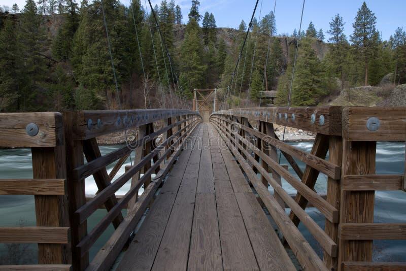 Houten hangbrug over rivier stock afbeelding